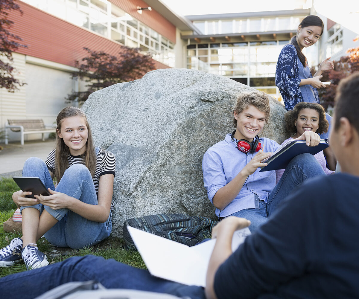 High school students studying hanging out on campus